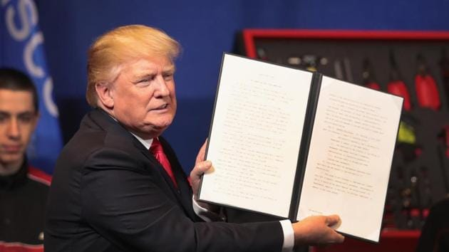 President Donald Trump signs an executive order to try to bring jobs back to American workers and revamp the H-1B visa guest worker program during a visit to the headquarters of tool manufacturer Snap-On on April 18, 2017 in Kenosha, Wisconsin.(AFP Photo)