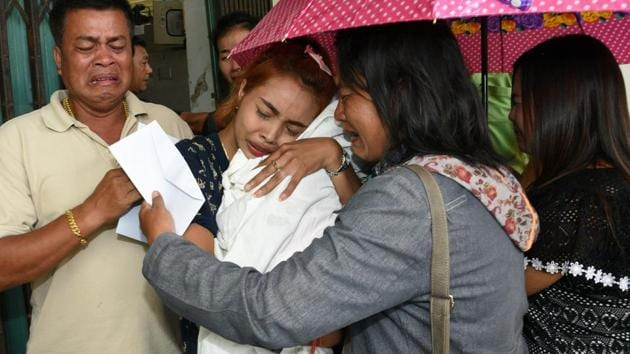 Jiranuch Trirat (centre) holds up the body of her 11-month-old daughter who was killed by her father, at a hospital in Phuket.(Reuters Photo)