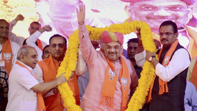 BJP national president Amit Shah being garlanded by Gujarat chief minister Vijay Rupani and deputy CM Nitin Patel at the BJP Vijay Vishwas Karyakarta Sammelan at Sabarmati riverfront in Ahmedabad, in this file photo from March 29, 2017.(PTI)