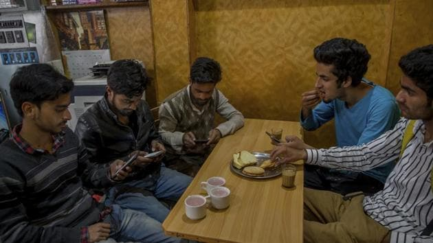 Kashmiri students browse internet on their mobile phones in Srinagar. By banning social media websites such as WhatsApp, Facebook, and Twitter, the government is encouraging people to find alternative ways of resistance, while inconveniencing millions of people who aren't trying to brew discontent.(AP)