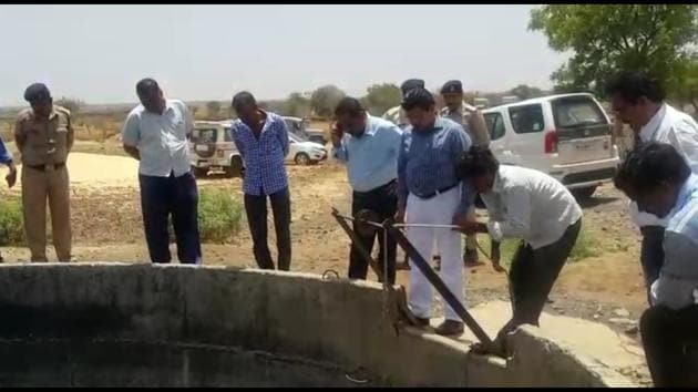 Officials stand around the well used by Dalits in Mana village in Agar Malwa district of Madhya Pradesh in which upper caste villagers allegedly poured kerosene.(HT PHOTO)