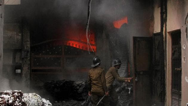 Firefighters trying to douse the flames at DG Kapoor Spinning Mill near Basti Jodhewal Chowk. The textile factory caught fire due to a short circuit on Saturday.(JS Grewal/HT Photo)