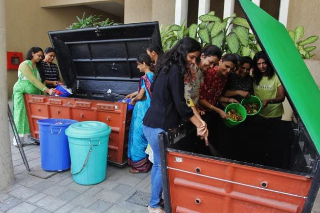 Residents of Marathon Onyx, Mulud, feed the two bio-bins with organic waste for producing compost.(Praful Gangurde/HT)