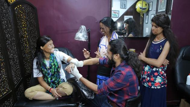 Acid attack survivor Rupa gets inked by tattoo-artist Vikas Malani, while survivors Laxmi and Ritu look on.(Manoj Verma/HT Photo)