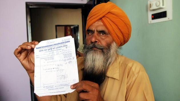 Hardeep Singh showing the de-addiction treatment slip of his son at their house in Jangpur village(Anil Dayal/HT Photo)