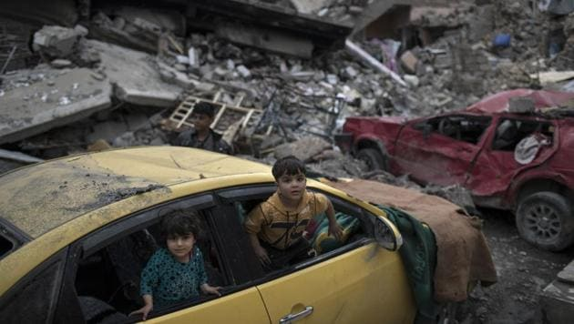 Children play inside a damaged car amid heavy destruction in a neighbourhood recently retaken by Iraqi security forces from Islamic State militants on the western side of Mosul.(AP)