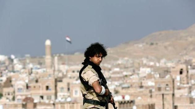A Houthi militant stands guard on the roof of a building overlooking a rally attended by supporters of the Houthi movement in Sanaa, Yemen in March. Al-Qaeda militants have on occasion fought alongside Yemeni government factions against the Houthis, one of its leaders said.(REUTERS FILE)