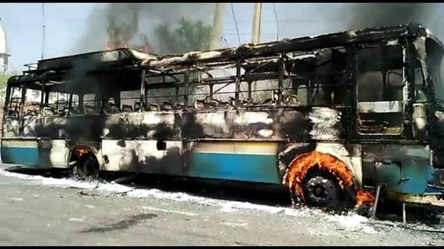 The Haryana Roadways bus torched by angry protesters after it crushed a Class12 student in Achina Tal village of Charkhi Dadri district on Monday.(Manoj Dhaka/HT Photo)