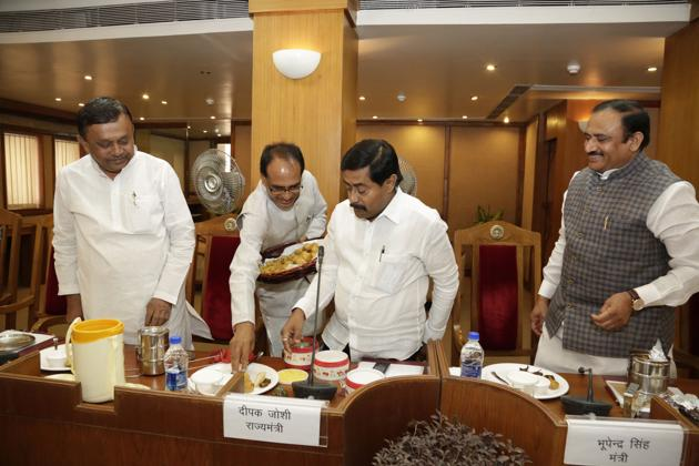 Chief minister Shivraj Singh Chouhan serving food to minister of state for technical education Deepak Joshi during a state cabinet meet at state secretariat on Tuesday.(HT Photo)