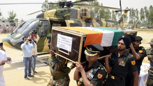 Indian Army personnel carry the body of Paramjeet Singh who was killed and mutilated in the attack on Monday.(Sameer Sehgal/HT Photo)