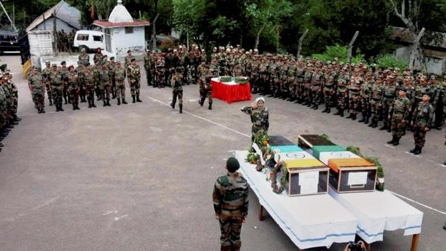 A senior army official pays respects to martyrs naib subedar Paramjit Singh and head constable Prem Sagar of BSF, on Tuesday in Jammu.(PTI Photo)