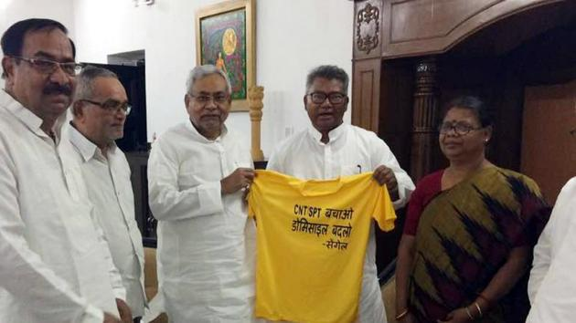 Bihar Chief Minister Nitish Kumar along with tribal leader and former MP Salkhan Murmu with a T-shirt displaying slogan against amendment in CNT and SPT Acts in Patna(HT Photo)