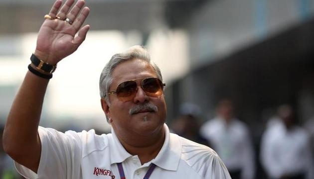 Vijay Mallya waves in the paddock during the third practice session of the Indian F1 Grand Prix at the Buddh International Circuit in Greater Noida, on the outskirts of New Delhi, on October 27, 2012. Banks are seeking to recover about $1.4 billion that the Indian authorities say Kingfisher owes. Mallya has repeatedly dismissed the charges against him and defended himself in messages on Twitter and rare interviews.(Reuters)