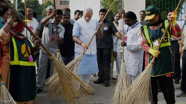 Prime Minister Narendra Modi wields a broom with NDMC workers to launch the Swachh Bharat Abhiyan in New Delhi in 2014.(PTI File Photo)