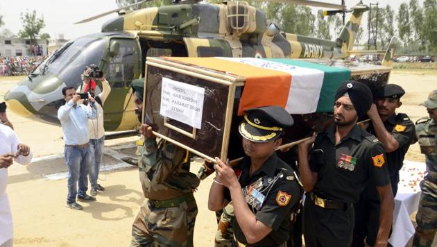 Indian Army personnel carry the coffin of soldier Paramjeet Singh ahead of his funeral at Vein Pein village near Amritsar.(Sameer Sehgal/ HT Photo)