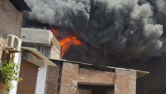 A huge cloud of smoke after fire engulfed one of the factories near Cheema Chowk, in Ludhiana on Monday.(HT Photo)