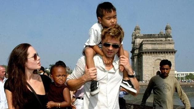 Angelina Jolie (L) holds daughter Zahara as husband and actor Brad Pitt (C) carries son Maddox during a stroll on the seafront promenade at the historic Gateway of India, (R) outside their hotel in Mumbai, 12 November 2006.(AFP)