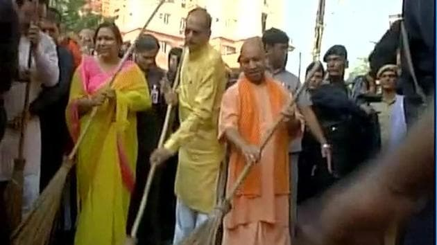 UP chief minister Yogi Adityanath sweeps road at a slum in Lucknow on Saturday to create awareness about cleanliness.(ANI Photo)