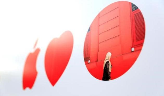 An Apple logo is shown next to a heart and a red dot depicting a local artist's work on the facade of Singapore's first Apple store on Friday.(Reuters photo)