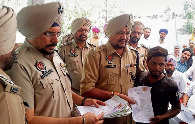 A villager handing over an affidavit, pledging to stay away from drugs, to SSP (rural) Surjit Singh at Khurshidpura village in Ludhiana on Saturday.(HT Photo)