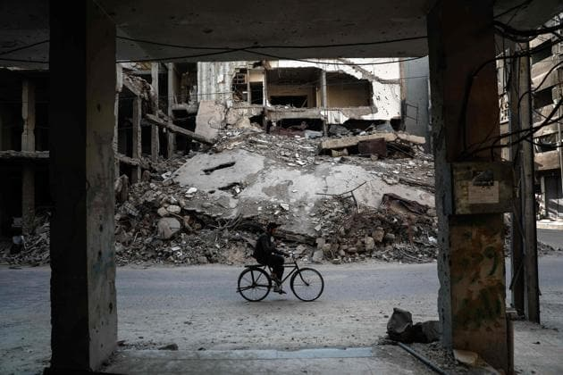 A Syrian man rides a bicycle past destroyed buildings in the rebel-held town of Douma.(AFP)