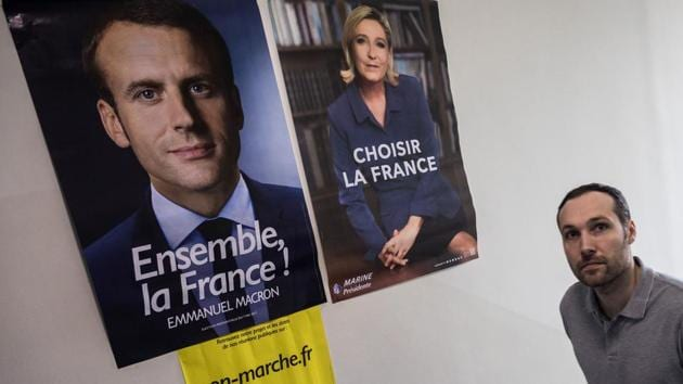 A man walks past posters of France's presidential election candidates Marine Le Pen and Emmanuel Macron at a polling station during the second round of France's presidential election in Hong Kong on May 7, 2017.(AFP Photo)