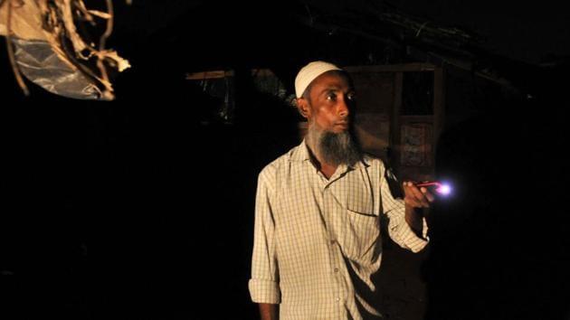 Kamal Hussain, a Rohingya Muslim, stands guard outside a settlement at night in Jammu.(Waseem Andrabi/HT Photo)