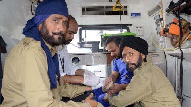 Medics administering first aid to firefighters with minor injuries which they sustained while trying to control a blaze at a textile factory near Cheema Chowk on Thursday.(Gurminder Singh/HT Photo)
