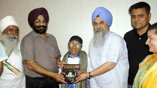 Dean, academic affairs, Gurnam Singh honouring athlete Mann Kaur at Punjabi University in Patiala on Thursday.(Bharat Bhushan/HT Photo)