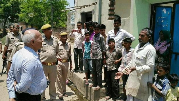 Uttar Pradesh home secretary Mani Prasad Mishra interacts with villagers in Shabeerpur on Wednesday.(HT file photo)