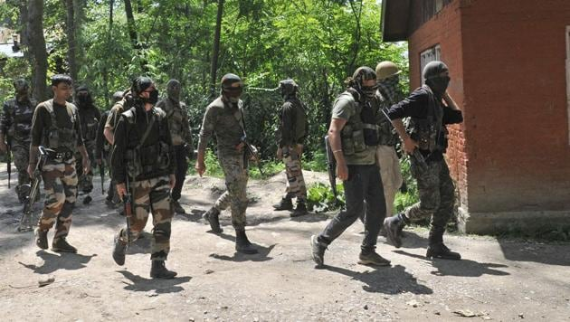Army soldiers and policemen patrol after an encounter, in which Hizbul commander Sabzar Ahmad Bhatwas killed, ends at Saimoh village in Tral, on May 27.(Waseem Andrabi / HT Photo)