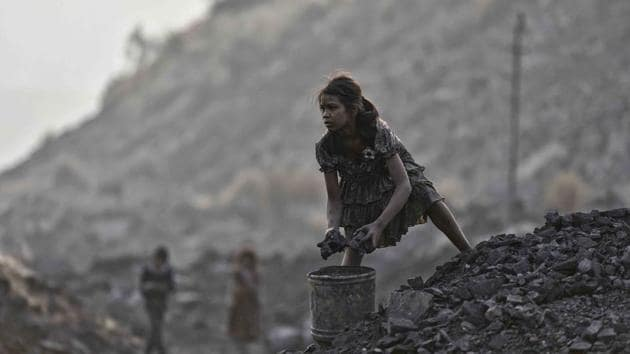A minor picks up chunks of coal from an open-cast mine in Jharkhand.(Ravi Choudhary/HT File)