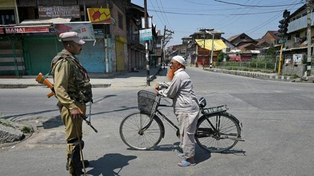A security personnel stops a cyclist in Srinagar after authorities imposed curfew in parts of the Valley following the killing of a top militant commander, Sabzar Bhat at Tral in Pulwama district of south Kashmir on Saturday.(PTI)