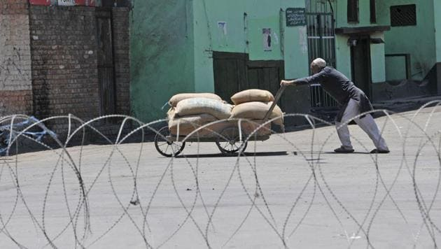 A Kashmiri man pushes his handcart near a barbed wire set up during curfew in downtown area of Srinagar. The government imposed strict curfew in parts of Srinagar on second consecutive day while the unified separatist leadership called for two-day shutdown across Kashmir.(Waseem Andrabi / Hindustan Times)