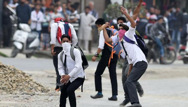Masked Kashmiri students throw stones during clashes with government forces in Srinagar.(AFP Photo)