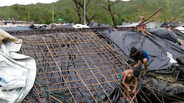 Rohingya refugee children fix the damaged roof of a hut in a makeshift camp in Bangladesh's Cox's Bazar district after Cyclone Mora made landfall in the region.(AFP Photo)