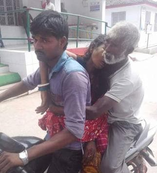Heart rending: LabourerShankar Sah holds the body of his wife, as son Pappu takes it home on a motorcycle.(HT photo)