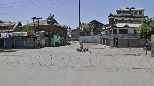 A policeman patrols near barbed wire set up as a barricade during curfew in downtown area of Srinagar.(Waseem Andrabi/Hindustan Times)