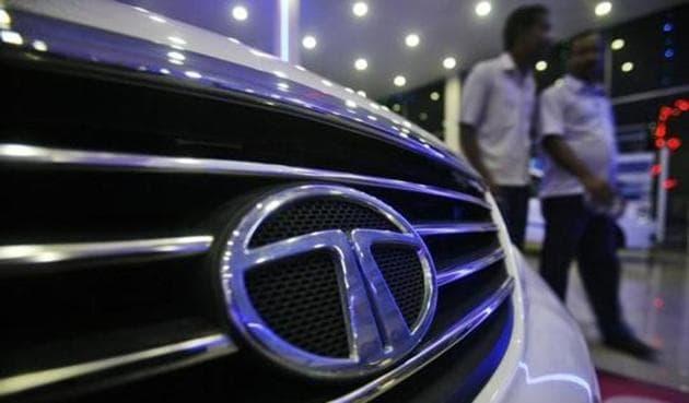 Men walk inside a Tata Motors showroom.(Reuters)