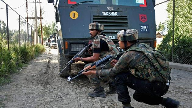 Army jawans take positions during an encounter with militants at Arwani village of Anantnag district of South Kashmir on Friday.(PTI Photo)