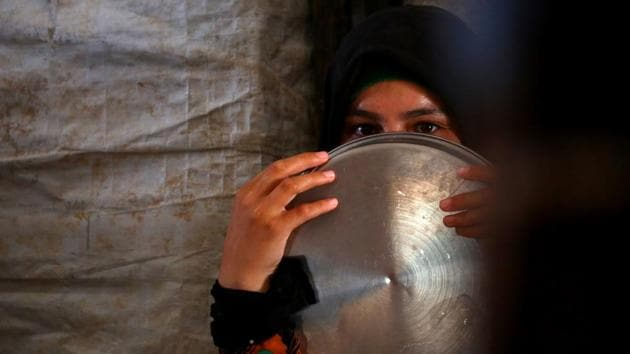 A displaced Syrian woman waits to receive food aid on June 9, 2017 at the al-Mabrouka camp in the village of Ras al-Ain on the Syria-Turkey border, where many Syrians who fled from territory held by the Islamic State (IS) group in Raqa are taking shelter. (AFP)