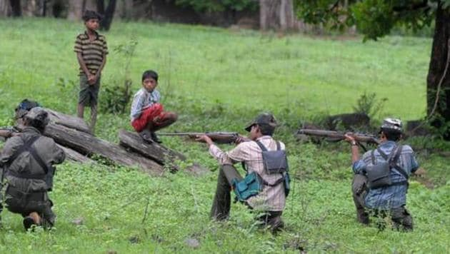 Representative image: Maoists watched by villagers as they ready their weapons.(AFP)