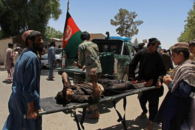 Afghan men carry a victim of the powerful car bomb in Lashkar Gah.(AFP)