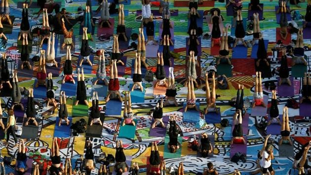 People practice yoga on 1500 yoga mats, printed with an artwork and placed together to form the artwork, during an event marking International Yoga Day, at Rabin Square in Tel Aviv, Israel June 21, 2017. REUTERS/Amir Cohen(REUTERS)