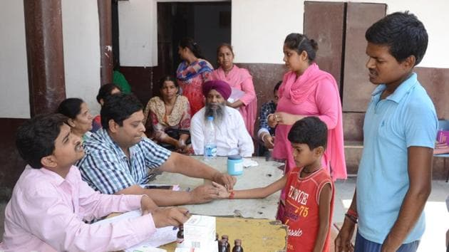 Health department officials examining patients at medical camp after diarrhoea outbreak in Makkar Colony in Ludhiana on Friday.(Jagtinder Singh Grewal / HT Photo)