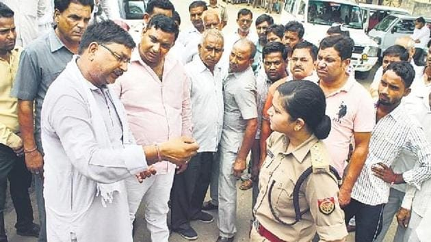Police officer Shrestha Thakur standing her ground against BJP protesters at the district court compound in Bulandshahr on Friday.(HT Photo)