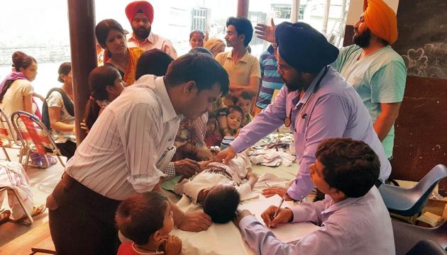 Doctors examining patients at a medical camp in Makkar Colony in Ludhiana on Sunday.(HT Photo)