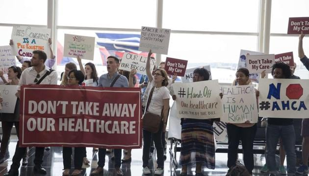 Protesters greet senators leaving Ronald Regan Washington National Airport in Washington, DC. People came out to voice their views on the upcoming healthcare vote on Capital Hill.(AFP File Photo)