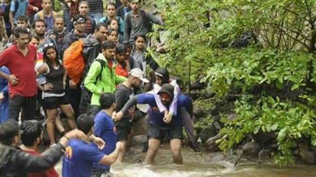 A group of 55, stuck at Devkund between two streams of the Kundalika river, was rescued after a six-hour operation.(HT)