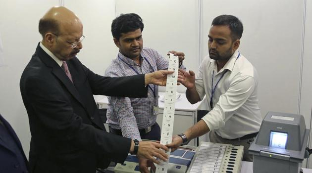 Election Commission head Nasim Zaidi, left, inspects an electronic voting machine in New Delhi on May 20.(AP Photo)